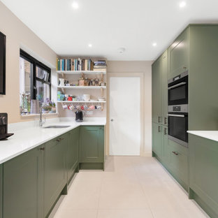 Inspiration for a mid-sized transitional u-shaped kitchen in London with an undermount sink, shaker cabinets, green cabinets, solid surface benchtops, panelled appliances, porcelain floors, no island, beige floor and white benchtop.