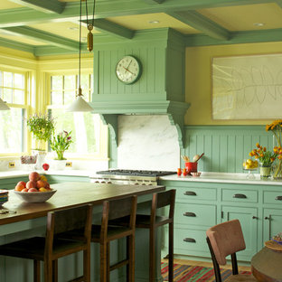 Cette image montre une cuisine américaine rustique en L avec un placard à porte affleurante, des portes de placard turquoises, un électroménager en acier inoxydable et un îlot central.