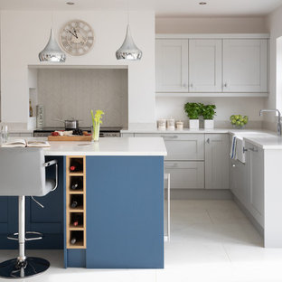 Photo of a traditional l-shaped kitchen in Other with a belfast sink, shaker cabinets, grey cabinets, stainless steel appliances, an island, white floors and white worktops.