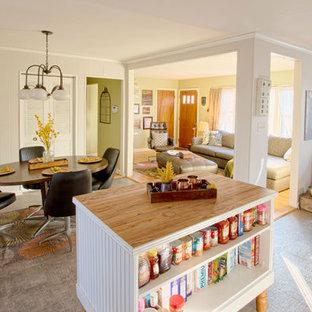 ローリーの中サイズのカントリー風おしゃれなキッチン (エプロンフロントシンク、フラットパネル扉のキャビネット、白いキャビネット、木材カウンター、グレーのキッチンパネル、磁器タイルのキッチンパネル、シルバーの調理設備の、クッションフロア) の写真