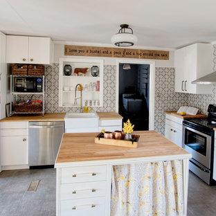 ローリーの中くらいのカントリー風おしゃれなキッチン (エプロンフロントシンク、フラットパネル扉のキャビネット、白いキャビネット、木材カウンター、グレーのキッチンパネル、磁器タイルのキッチンパネル、シルバーの調理設備、クッションフロア) の写真