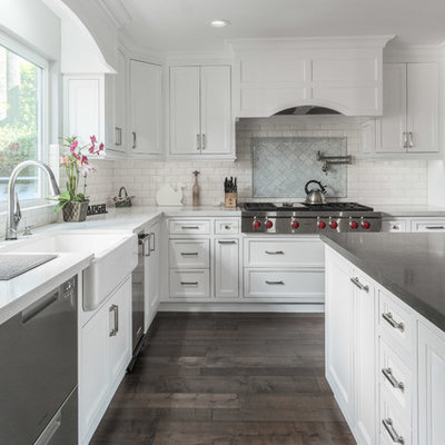 Transitional l-shaped dark wood floor and brown floor kitchen photo in Los Angeles with a farmhouse sink, recessed-panel cabinets, white cabinets, white backsplash, subway tile backsplash, stainless steel appliances, an island and white countertops