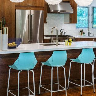 Cette image montre une cuisine design en L de taille moyenne avec un placard à porte plane, une crédence blanche, un électroménager en acier inoxydable, un sol en carreaux de ciment, un îlot central, un sol gris, un évier 3 bacs, des portes de placard en bois brun et un plan de travail blanc.