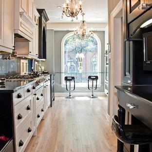 デトロイトの中サイズのヴィクトリアン調のおしゃれなキッチン (シェーカースタイル扉のキャビネット、白いキャビネット、パネルと同色の調理設備、淡色無垢フローリング) の写真