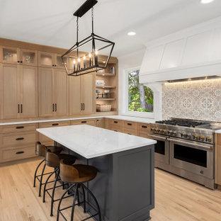 Bild på ett stort lantligt vit vitt kök, med en rustik diskho, skåp i shakerstil, skåp i ljust trä, bänkskiva i kvarts, vitt stänkskydd, stänkskydd i cementkakel, rostfria vitvaror, ljust trägolv och flera köksöar