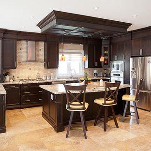 Foto di una cucina chic di medie dimensioni con ante con riquadro incassato, top in granito, paraspruzzi beige, paraspruzzi con piastrelle in pietra, elettrodomestici in acciaio inossidabile e un'isola