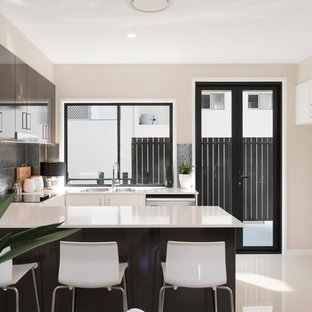 Photo of a small modern u-shaped open plan kitchen in Brisbane with a double-bowl sink, flat-panel cabinets, quartz benchtops, metallic splashback, ceramic splashback, stainless steel appliances, porcelain floors, a peninsula and white cabinets.