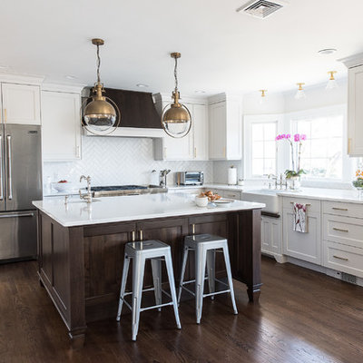 Eat-in kitchen - mid-sized transitional l-shaped brown floor and medium tone wood floor eat-in kitchen idea in New York with a farmhouse sink, white cabinets, white backsplash, stainless steel appliances, an island, flat-panel cabinets, quartz countertops, ceramic backsplash and white countertops