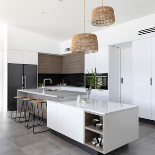 Inspiration for a large contemporary l-shaped open plan kitchen in Brisbane with a single-bowl sink, flat-panel cabinets, white cabinets, quartz benchtops, multi-coloured splashback, ceramic splashback, black appliances, cement tiles, with island, grey floor and grey benchtop.