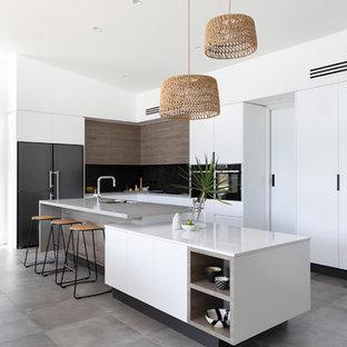 Offene, Große Moderne Küche in L-Form mit Waschbecken, flächenbündigen Schrankfronten, weißen Schränken, Quarzwerkstein-Arbeitsplatte, bunter Rückwand, Rückwand aus Keramikfliesen, schwarzen Elektrogeräten, Zementfliesen, Kücheninsel, grauem Boden und grauer Arbeitsplatte in Brisbane