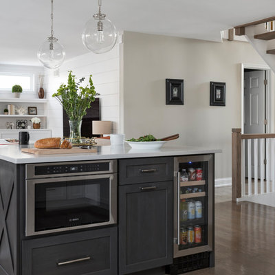 Inspiration for a mid-sized transitional u-shaped medium tone wood floor and gray floor open concept kitchen remodel in Chicago with a farmhouse sink, shaker cabinets, white cabinets, quartz countertops, white backsplash, marble backsplash, stainless steel appliances, an island and gray countertops