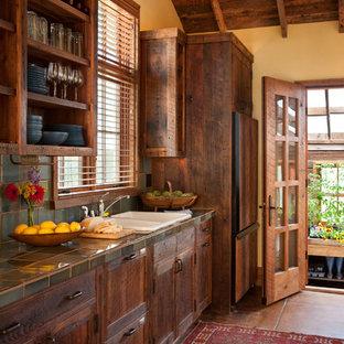 Urige Küche mit Einbauwaschbecken, dunklen Holzschränken, Arbeitsplatte aus Fliesen, Küchenrückwand in Blau und Küchengeräten aus Edelstahl in Sonstige