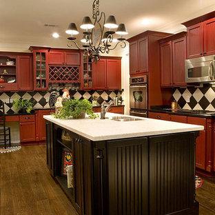 インディアナポリスの中サイズのトラディショナルスタイルのおしゃれなキッチン (アンダーカウンターシンク、シェーカースタイル扉のキャビネット、赤いキャビネット、御影石カウンター、黒いキッチンパネル、セラミックタイルのキッチンパネル、シルバーの調理設備の、濃色無垢フローリング) の写真