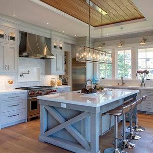 Coastal kitchen ideas - Kitchen - coastal light wood floor kitchen idea in New York with an undermount sink, shaker cabinets, gray cabinets, gray backsplash, stainless steel appliances and an island