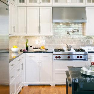 Cette photo montre une cuisine victorienne avec un placard avec porte à panneau encastré, un électroménager en acier inoxydable, des portes de placard blanches, une crédence métallisée et une crédence en carrelage métro.
