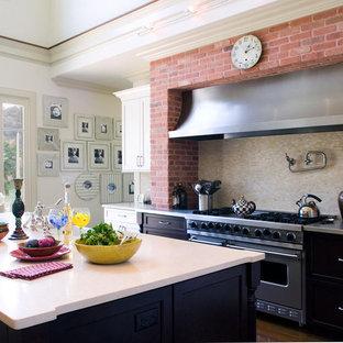 Große Shabby-Look Küche in L-Form mit schwarzen Schränken, Edelstahl-Arbeitsplatte, Küchenrückwand in Beige, Rückwand aus Mosaikfliesen, Küchengeräten aus Edelstahl, braunem Holzboden, Kücheninsel, Landhausspüle und Schrankfronten im Shaker-Stil in New York