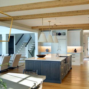 Идея дизайна: огромная угловая кухня-гостиная в классическом стиле с раковиной в стиле кантри, фасадами с утопленной филенкой, белыми фасадами, гранитной столешницей, белым фартуком, фартуком из гранита, техникой под мебельный фасад, светлым паркетным полом, островом и белой столешницей