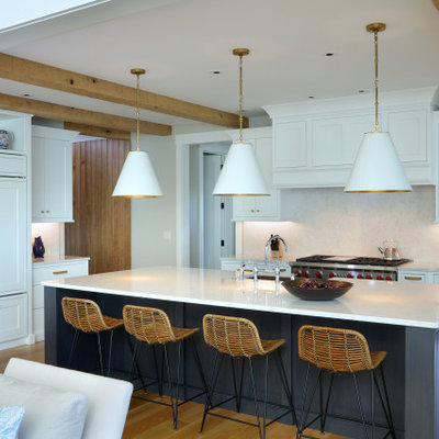 Example of a huge transitional l-shaped light wood floor and brown floor open concept kitchen design in Grand Rapids with a farmhouse sink, recessed-panel cabinets, white cabinets, granite countertops, white backsplash, granite backsplash, paneled appliances, an island and white countertops