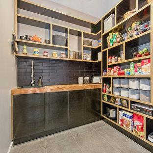 Удачное сочетание для дизайна помещения: большая параллельная кухня-гостиная в стиле фьюжн с двойной раковиной, плоскими фасадами, черными фасадами, столешницей из бетона, черным фартуком, фартуком из плитки кабанчик, техникой из нержавеющей стали, паркетным полом среднего тона, островом, коричневым полом и зеленой столешницей - самое интересное для вас