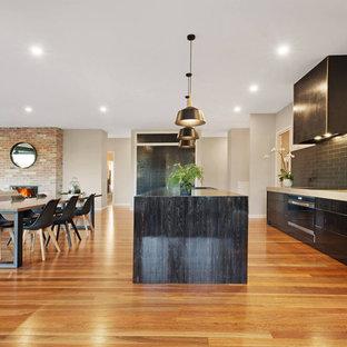 Неиссякаемый источник вдохновения для домашнего уюта: большая параллельная кухня-гостиная в стиле фьюжн с двойной раковиной, плоскими фасадами, черными фасадами, столешницей из бетона, черным фартуком, фартуком из плитки кабанчик, техникой из нержавеющей стали, паркетным полом среднего тона, островом, коричневым полом и зеленой столешницей
