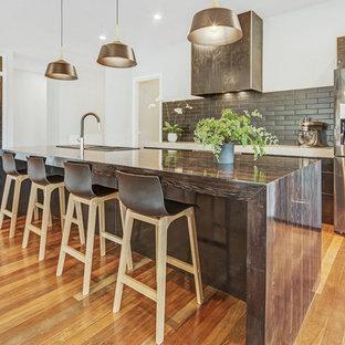 Создайте стильный интерьер: большая параллельная кухня-гостиная в стиле фьюжн с двойной раковиной, плоскими фасадами, черными фасадами, столешницей из бетона, черным фартуком, фартуком из плитки кабанчик, техникой из нержавеющей стали, паркетным полом среднего тона, островом, коричневым полом и зеленой столешницей - последний тренд