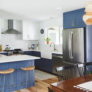 Mid-sized modern eat-in kitchen inspiration - Example of a mid-sized minimalist u-shaped light wood floor and brown floor eat-in kitchen design in Austin with a farmhouse sink, shaker cabinets, blue cabinets, quartz countertops, white backsplash, ceramic backsplash, stainless steel appliances, a peninsula and white countertops