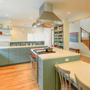 This is an example of a mid-sized midcentury l-shaped eat-in kitchen in Austin with an undermount sink, flat-panel cabinets, green cabinets, quartz benchtops, grey splashback, ceramic splashback, stainless steel appliances, medium hardwood floors and with island.