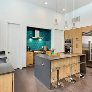 Mid-sized contemporary open concept kitchen ideas - Example of a mid-sized trendy u-shaped bamboo floor open concept kitchen design in Austin with a farmhouse sink, flat-panel cabinets, light wood cabinets, quartz countertops, green backsplash, glass tile backsplash, stainless steel appliances and an island