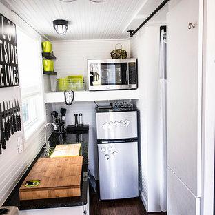 Пример оригинального дизайна: отдельная, параллельная кухня в стиле фьюжн с белыми фасадами и техникой из нержавеющей стали