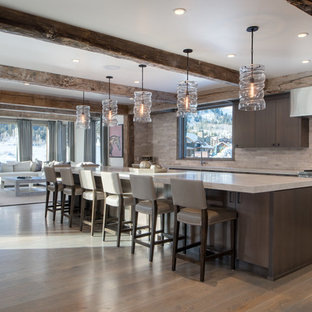 Rustic open concept kitchen ideas - Inspiration for a rustic single-wall medium tone wood floor and brown floor open concept kitchen remodel in Other with flat-panel cabinets, dark wood cabinets, beige backsplash, stainless steel appliances and an island