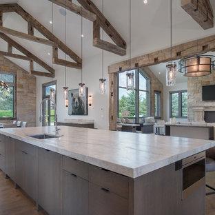 Foto de cocina comedor rural con armarios con paneles lisos, encimera de cuarcita, salpicadero de losas de piedra, electrodomésticos de acero inoxidable y una isla