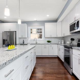 Große Klassische Wohnküche in L-Form mit Doppelwaschbecken, Schrankfronten im Shaker-Stil, weißen Schränken, Granit-Arbeitsplatte, Küchenrückwand in Weiß, Rückwand aus Metrofliesen, Küchengeräten aus Edelstahl, Laminat, Kücheninsel, braunem Boden und grauer Arbeitsplatte in Baltimore