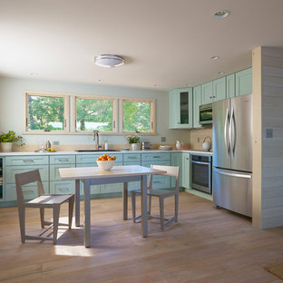 Inspiration for a mid-sized beach style l-shaped eat-in kitchen in Portland Maine with shaker cabinets, blue cabinets, beige splashback, timber splashback, stainless steel appliances, light hardwood floors, no island, brown floor, a drop-in sink and laminate benchtops.