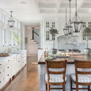 Foto di una cucina costiera con lavello stile country, ante di vetro, ante bianche, paraspruzzi bianco, paraspruzzi in lastra di pietra, elettrodomestici in acciaio inossidabile, pavimento in legno massello medio, isola e top bianco