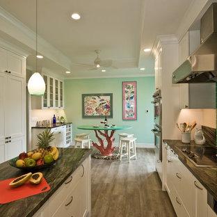 ハワイのトロピカルスタイルのおしゃれなアイランドキッチン (シェーカースタイル扉のキャビネット、白いキャビネット、御影石カウンター、緑のキッチンパネル、ガラスタイルのキッチンパネル、パネルと同色の調理設備、クッションフロア) の写真