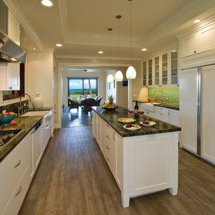 ハワイのトロピカルスタイルのおしゃれなアイランドキッチン (エプロンフロントシンク、シェーカースタイル扉のキャビネット、白いキャビネット、御影石カウンター、緑のキッチンパネル、ガラスタイルのキッチンパネル、パネルと同色の調理設備、クッションフロア) の写真