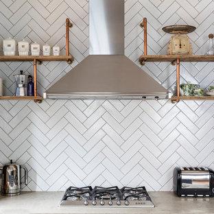 ロンドンの大きいインダストリアルスタイルのおしゃれなキッチン (ドロップインシンク、シェーカースタイル扉のキャビネット、グレーのキャビネット、コンクリートカウンター、カラー調理設備、無垢フローリング) の写真