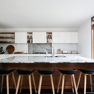 Design ideas for a large contemporary l-shaped kitchen in Melbourne with an undermount sink, white cabinets, granite benchtops, multi-coloured splashback, stone slab splashback, stainless steel appliances, with island, black floor, flat-panel cabinets and multi-coloured benchtop.
