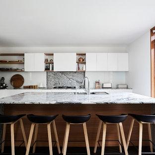 Idee per una grande cucina a L minimal con lavello sottopiano, ante bianche, top in granito, paraspruzzi multicolore, paraspruzzi in lastra di pietra, elettrodomestici in acciaio inossidabile, isola, pavimento nero, ante lisce e top multicolore