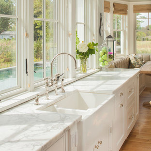 Example of a large beach style light wood floor eat-in kitchen design in New York with a farmhouse sink, recessed-panel cabinets, white cabinets, marble countertops and white countertops