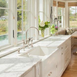 Inspiration pour une grande cuisine américaine marine avec un évier de ferme, un placard avec porte à panneau encastré, des portes de placard blanches, un plan de travail en marbre, un sol en bois clair et un plan de travail blanc.
