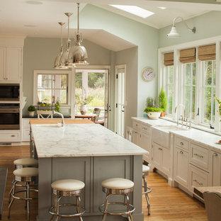 ニューヨークの広いビーチスタイルのおしゃれなキッチン (エプロンフロントシンク、落し込みパネル扉のキャビネット、白いキャビネット、大理石カウンター、白いキッチンパネル、シルバーの調理設備、淡色無垢フローリング) の写真