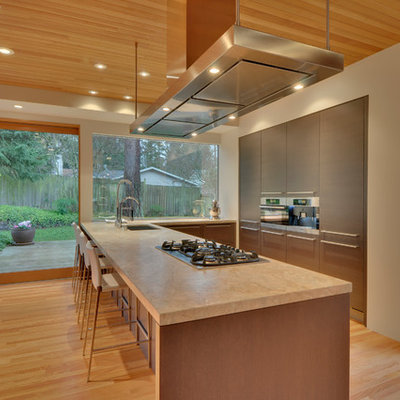Inspiration for a modern u-shaped kitchen remodel in Seattle with solid surface countertops, flat-panel cabinets and paneled appliances