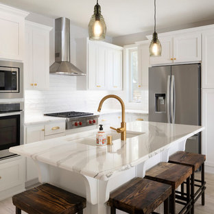 Mid-sized transitional kitchen designs - Example of a mid-sized transitional l-shaped light wood floor and beige floor kitchen design in Minneapolis with white cabinets, white backsplash, stainless steel appliances, an island, white countertops, a double-bowl sink, shaker cabinets and subway tile backsplash