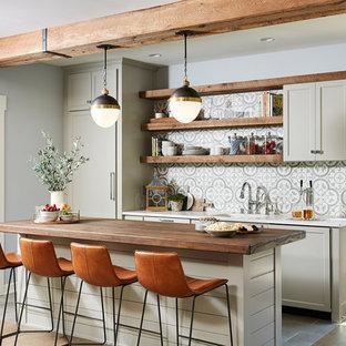 Réalisation d'une cuisine marine avec un évier encastré, un placard à porte shaker, des portes de placard grises, une crédence multicolore, un électroménager encastrable, un îlot central, un sol gris et un plan de travail blanc.