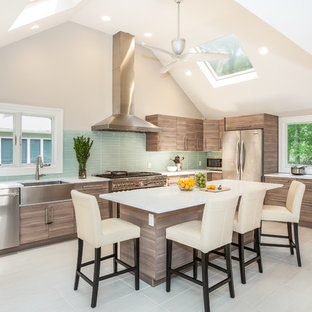 This is an example of a mid-sized contemporary l-shaped kitchen in Newark with a farmhouse sink, flat-panel cabinets, grey cabinets, quartz benchtops, green splashback, glass tile splashback, stainless steel appliances, porcelain floors, with island and white floor.