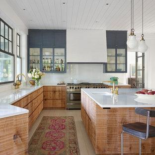 他の地域のビーチスタイルのおしゃれなキッチン (アンダーカウンターシンク、フラットパネル扉のキャビネット、中間色木目調キャビネット、白いキッチンパネル、シルバーの調理設備、ベージュの床、白いキッチンカウンター、淡色無垢フローリング) の写真