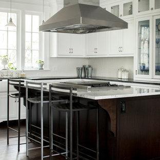 Exemple d'une cuisine victorienne en L avec un évier de ferme, un placard à porte shaker, des portes de placard blanches, une crédence blanche, un électroménager encastrable, un sol en bois foncé et un îlot central.
