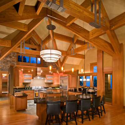 Example of a large mountain style u-shaped medium tone wood floor and brown floor eat-in kitchen design in Other with glass-front cabinets, medium tone wood cabinets, stainless steel appliances, a farmhouse sink, granite countertops, beige backsplash and two islands