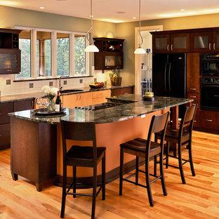 Immagine di una cucina contemporanea con ante di vetro, elettrodomestici neri, top in granito e ante in legno bruno
